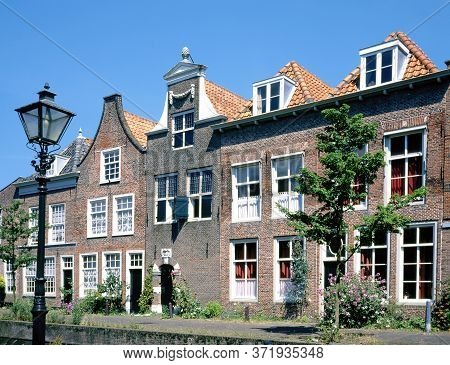 Houses With Stepped Gables And At Foreground An Old Fashioned Lamppost Along A Canal In Leiden, The
