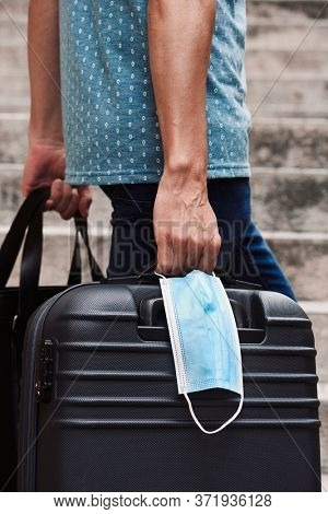 closeup of a young man on the street, in casual wear, carrying a black leather travel bag in one hand and a gray suitcase and a surgical mask in the other hand, while is climbing an outdoor stairway