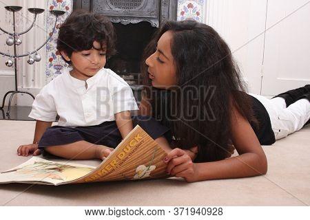 An Older Sibling Reads To Her Baby Brother In Witney, Oxfordshire, Uk. Taken On 08 27 2008