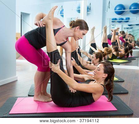 Aeróbica Pilates personal trainer ajudando o grupo de mulheres em uma classe de ginástica