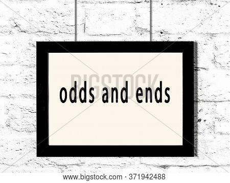 Black Wooden Frame With Inscription Odds And Ends Hanging On White Brick Wall