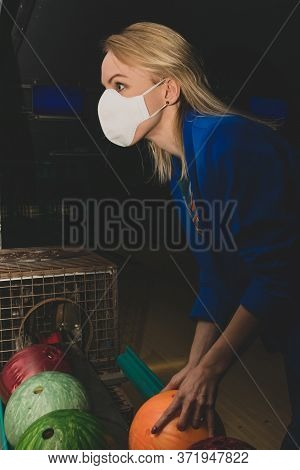 Leisure And Health Care Concept. Blonde Woman With Medicine Mask And Blue Jacket Picking Bowling Bal
