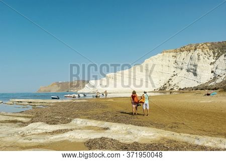 couple of tourist looking at white cliff in southern coast of Sicily natural landmark