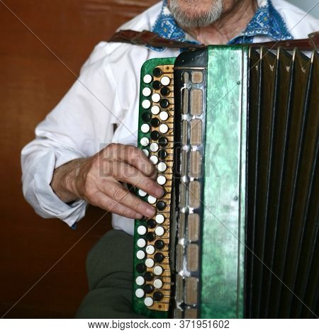 Grandfather Plays The Harmonica. Grandfather In A White Shirt. The Accordion Is White. Square Frame.