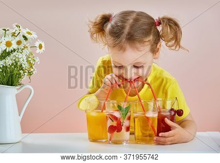A Cheerful Beautiful Girl In A Yellow T-shirt With Several Soft Drinks Drinks Cocktails From Several