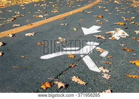 Painted White Pedestrian Symbol With Arrow On Asphalt Road At City Street Or Park On Autumn Day. Ded