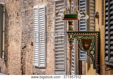 Siena, Italy, April 2018: Street Lamp Of The Goose District In Siena. Tuscany, Italy. Each Colour An