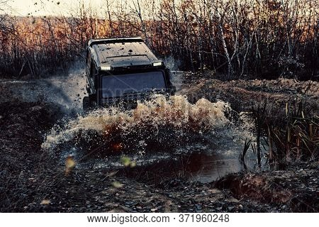 4x4 Concept. Suv Or Offroader On Mud Road. Large Rocks On The Road Extreme Travel Adventure In Natur
