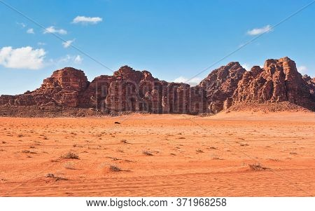 Red Dusty Desert With Large Rock Massif And Blue Sky In Background, Small Off Road Vehicle In Foregr