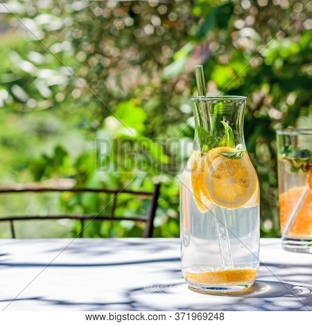 Cold Refreshing Summer Drink Or Cocktail In Carafe With Glass Straw. Detox Water Or Lemonade With Sl