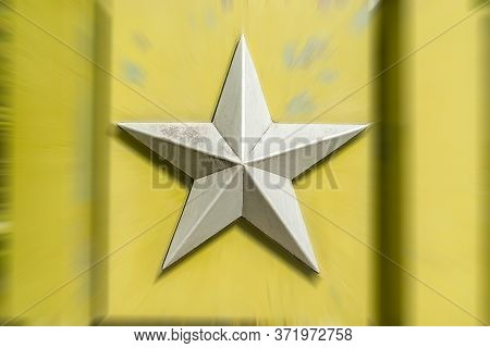 Silver Metal Five Pointed Soviet Star On A Blurred Background Of Light Greenish Yellow Color