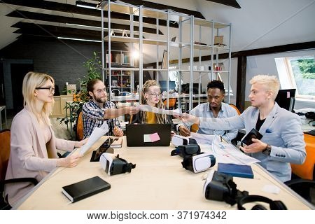 Team Of Casually Dressed Businesspeople Discussing Ideas In The Office. Creative Multiethnical Profe