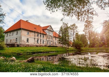 Municipal School In An Old Building With A Pond In The Yard. Historic Old Manor, Pope, Latvia