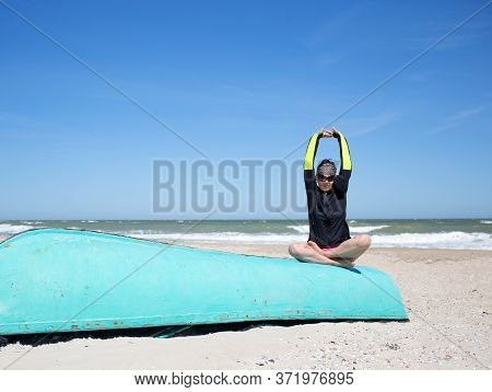 Woman In Windbreaker And Sunglasses Sit At Windy Sand Sea Beach On Old Blue Boat In Yoga Lotus Padma