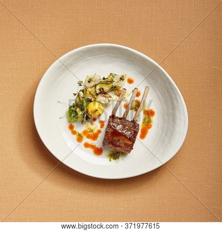 Rack of lamb in white deep plate topview. Luxury restaurant main course. Fancy dish top view. Mutton ribs. Meat piece served in bowl. Roasted meat with vegetable garnish. Culinary art