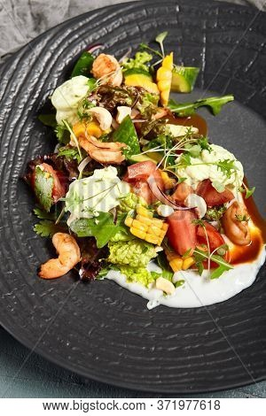 Delicious salads served on plates side view. Restaurant dishes, trendy salads with shellfish and vegetables with old silverware on grey texture background