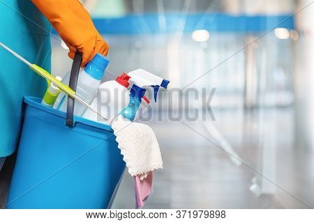 The Concept Of Cleaning Services. A Cleaning Lady Is Holding A Bucket Of Cleaning Products.