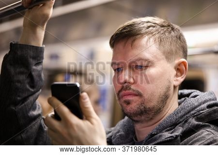 Guy Reads From Smartphone In Public Transport. Accurate Location Using Map Application. Public Trans