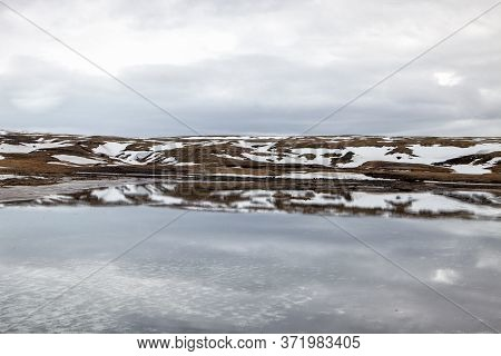 The Mountain\'s Reflection Is Seen In The Snow Melt In Iceland