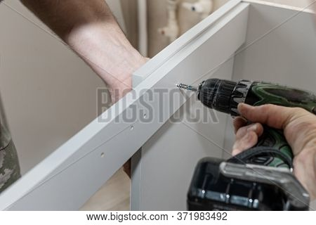 Master Builds A Furniture Cabinet. Mounting For Furniture Panels. Assembling The Cabinet Door Mechan