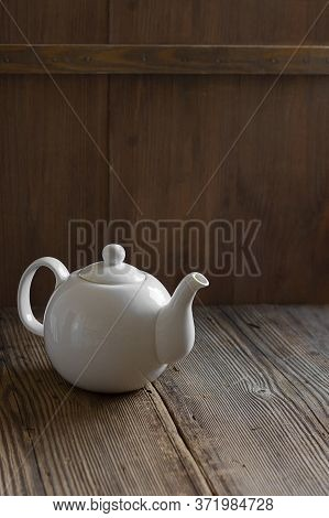 White Ceramic Mockup Teapot For Hot Tea On Empty Old Wooden Table Near Wall Made Of Brown Timber Pla
