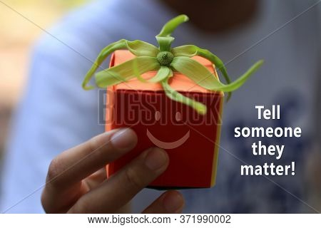 Inspirational Motivational Quote - Tell Someone They Matter. With Hand Holding An Orange Gift Box Wi