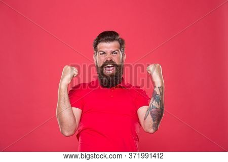 Power Of Happiness. Happy Hipster Make Winner Gesture. Bearded Man Celebrate Victory Red Background.