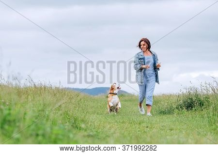 Happy Smiling Jogging Female With Fluttering Hairs And Her Beagle Dog Running And Looking At Eyes. W