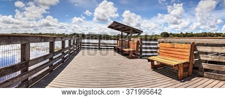 Boardwalk With Benches Overlooking The Flooded Swamp Of Myakka River State Park In Sarasota, Florida