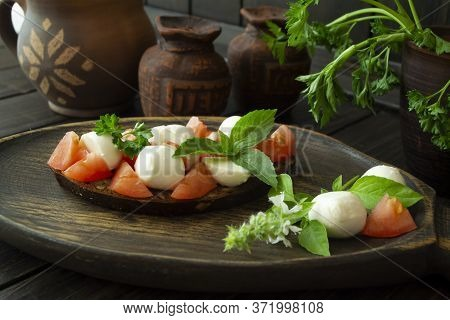 Bruschetta With Tomatoes, Mozzarella And Basil. Traditional Italian Appetizer Or Snack, Antipasto