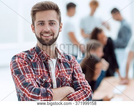 smiling young man standing in a modern office
