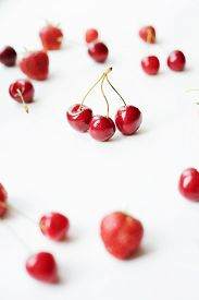 Vertical Photo Of Strawberries And Cherries Scattered On A White Table. Triple Cherry Branch.