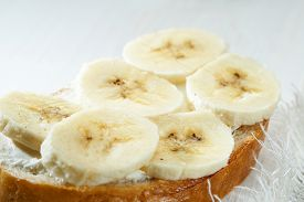 Sandwich With Banana Slices Close Up On White Wooden Table.