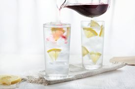 Two Glasses Of Ice Cold Lemonade On Linen Napkin On White Background In Blur.