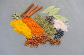 On A Grey Background. Festive Composition Made Of Cinnamon, Pepper, Anise, Turmeric And Pink Salt. T