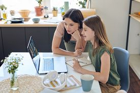 Mother watching how daughter working with other students in group video chat with teacher
