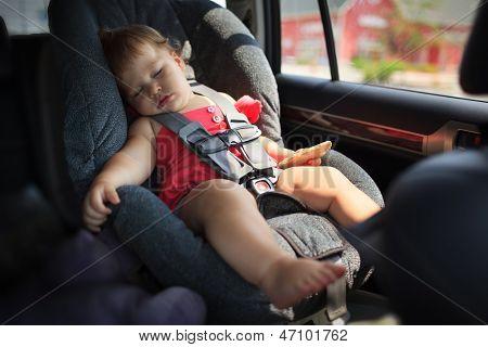 Toddler girl sleeping in child car seat.