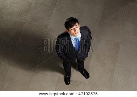 Bild der junge Geschäftsmann mit seinen Augen geschlossen oben suchen. Ansicht von oben