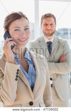Pretty businesswoman having phone conversation with partner behind her