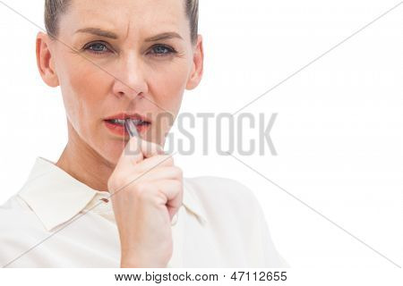 Worried businesswoman with pen on mouth looking at the camera