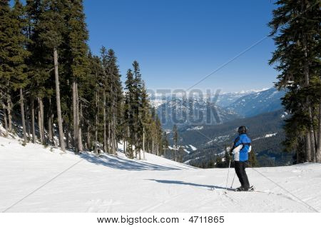 Skier Stopped On Trail, Looking At Mountains