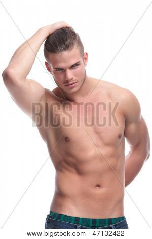 young fashion topless man holding a hand at his back and holding his hair with the other. isolated on white background