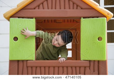 Child Playing In Toy House