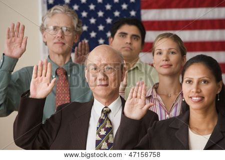 Adults raising their right hands before American flag