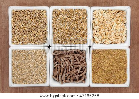 Cereal food selection in white porcelain dishes over papyrus background.