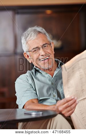Happy senior man with glasses reading newspaper in caf���©