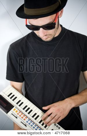 Cool Guy With Hat Playing On Tiny Keyboard