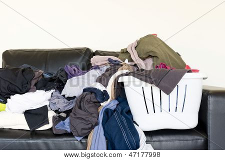 Housework concept of a large pile of laundry dumped on the couch waiting to be folded and put away poster
