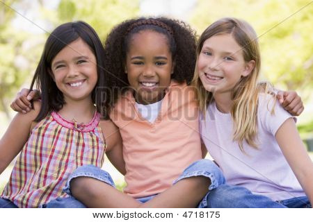 Three young girl friends sitting outdoors arms around eachother smiling poster