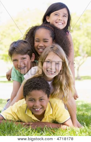 Five young friends piled up on top of each other outdoors smiling poster